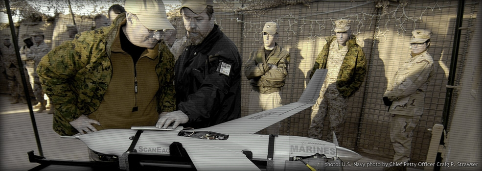 A contractor working for the Marine Corps explains to Secretary of the Navy Donald C. Winter the operation and capabilities of the unmanned aerial vehicle Scan Eagle at Al Qaim, Iraq.